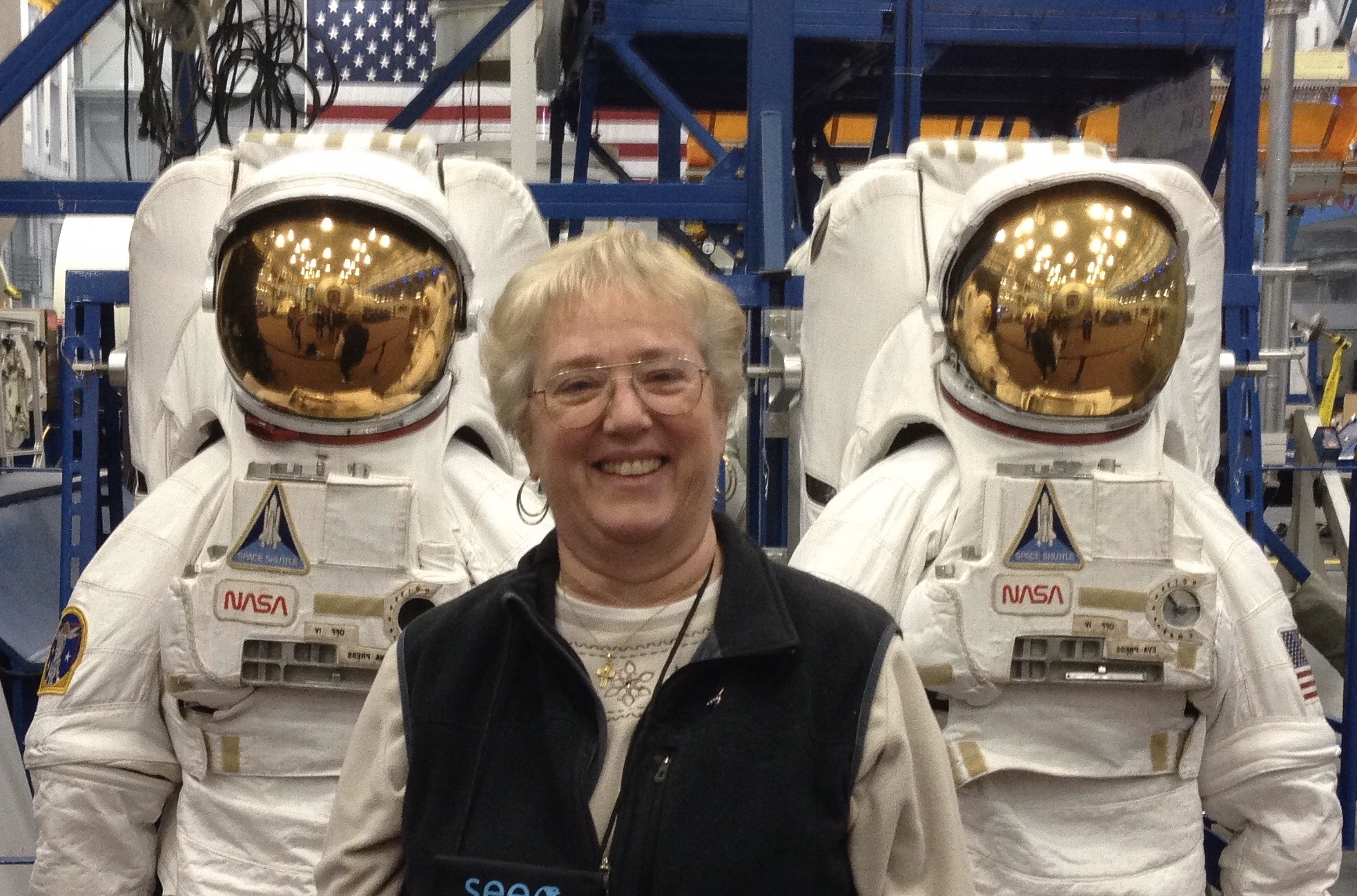Sharon Eggleston poses with astronaut suits at Johnson Space Center