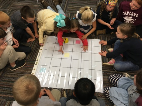Several children program the Bee Bot to land on the correct answer square on the mat.