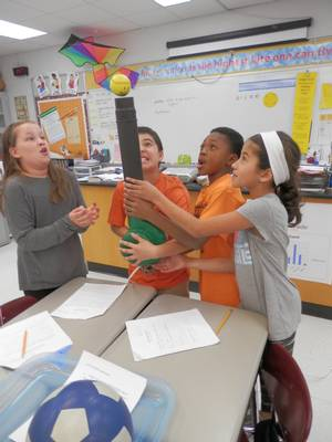 Classroom students demonstrating with Bernoulli's principle with tennis ball