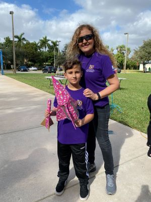 Dr. Chiarella poses with a student and model rockets