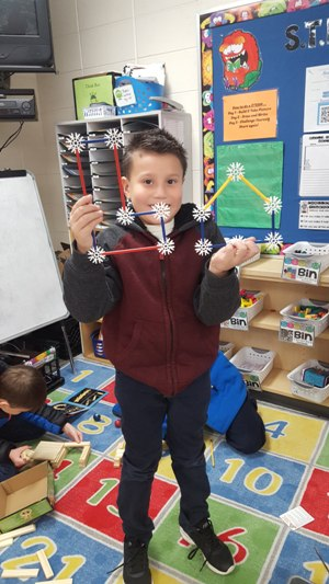 A student in a classroom holds up geometric shapes he made with the middle school math STEM Kit.