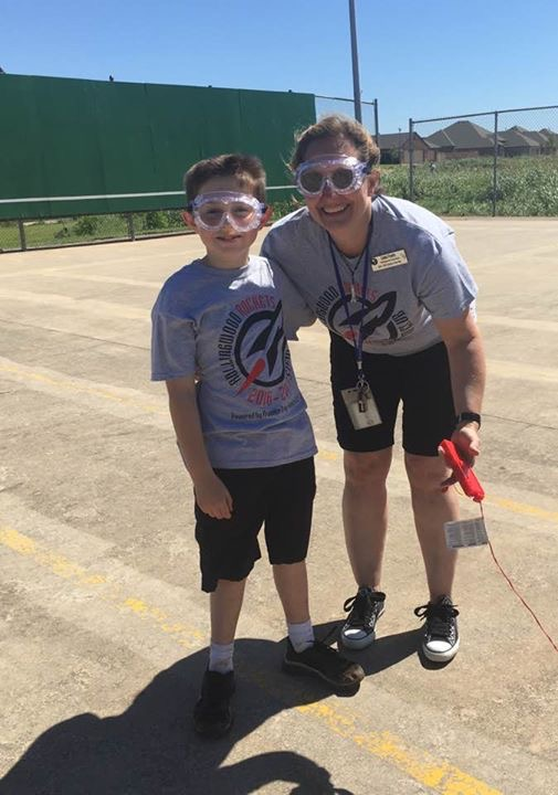 Teacher and student wear goggles as they get ready to launch a rocket.