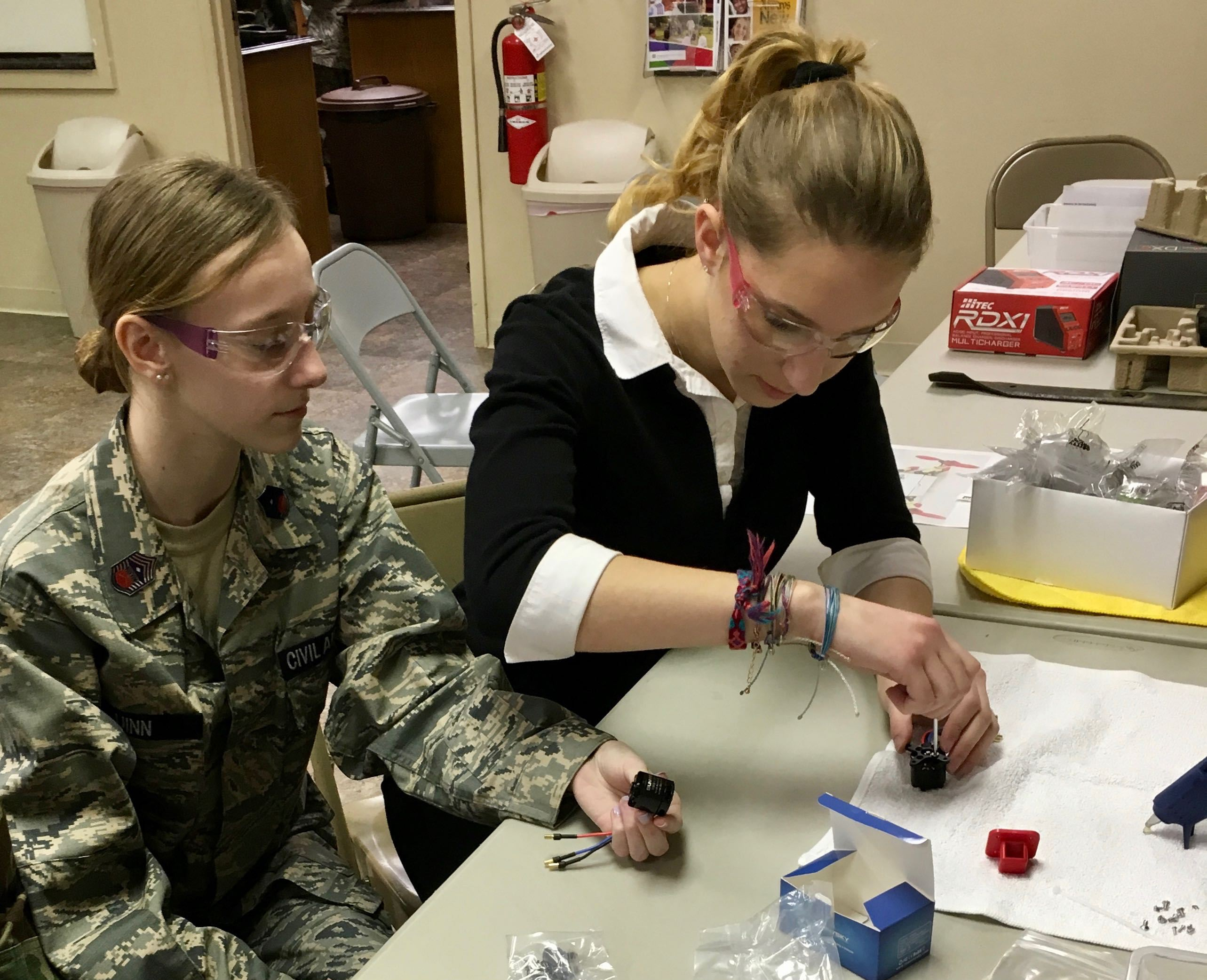 Cadets worki with STEM kit while wearing safety goggles.