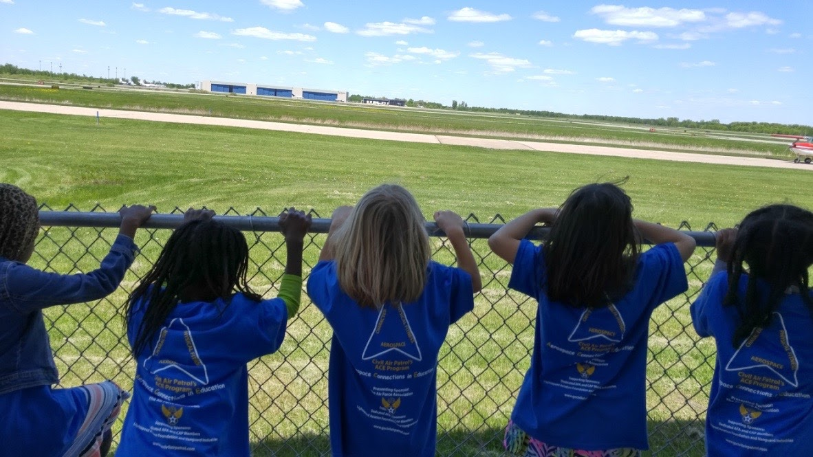 Students watch planes on a runway