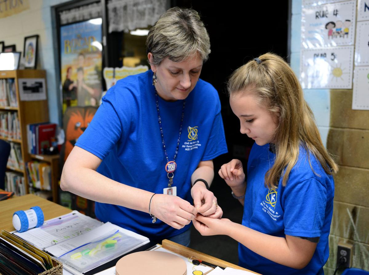 Teacher Suzanne Costner assists student with STEM project